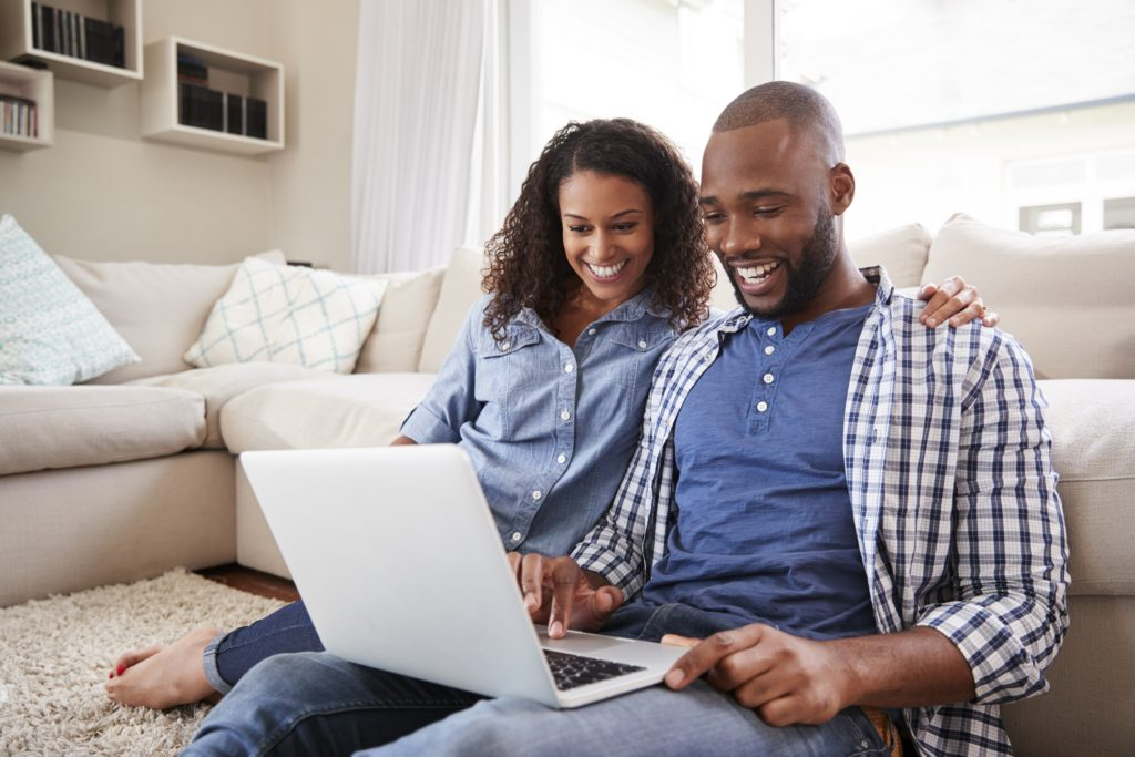 A man and woman smiling together while looking at a laptop and sitting on the floor
